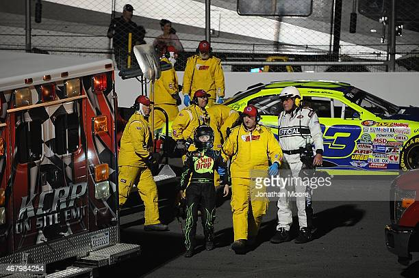 Nicole Behar driver of the Custom Welding Fabrication Inc Chevrolet is escorted by medical personal after wrecking during the Napa Auto Parts 150 at...