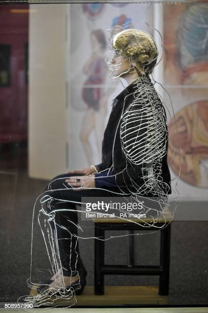 Nicole Briggs from @Bristol science attraction sits behind a real human brain suspended in liquid with a toscale skeleton central nervous system and...