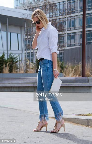 Nicole Craven wearing faded denim jeans with frayed hem by 3x1 JCrew white shirt nude strappy sandals by Joe's Jeans Cuyana white leather clutch bag...