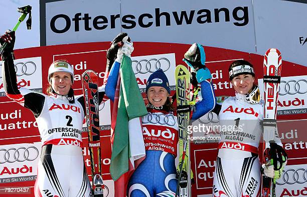 Nicole Hosp of Austria second place Denise Karbon of Italy first place and Elisabeth Goergl of Austria third place celebrate on the podium after the...