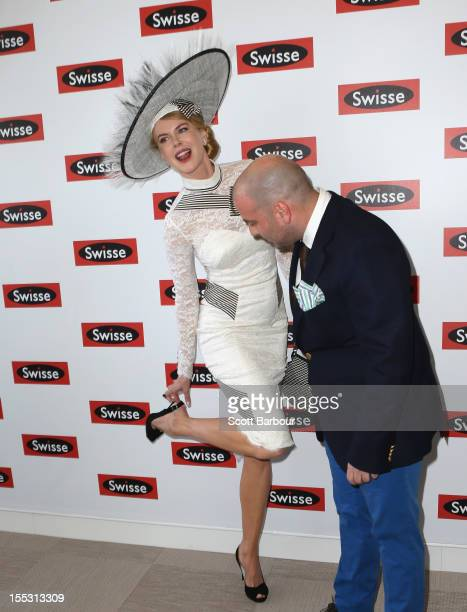 Nicole Kidman adjusts her shoes as celebrity chef George Calombaris looks on as they attend the Swisse marquee on Derby Day at Flemington Racecourse...