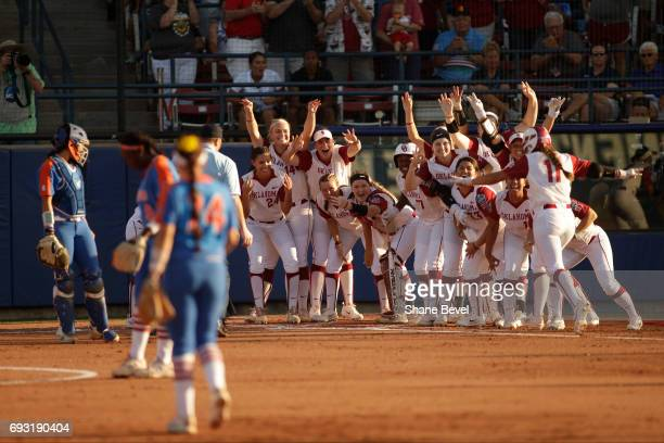 Nicole Mendes of the University of Oklahoma arrives at home plate to her cheering teammates after hitting a home run against the University of...