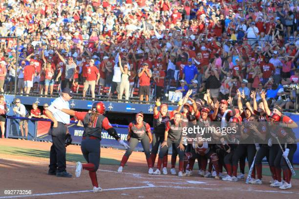 Nicole Mendes of The University of Oklahoma meets her team at home plate as she scores a run during Game 1 of the Division I Women's Softball...