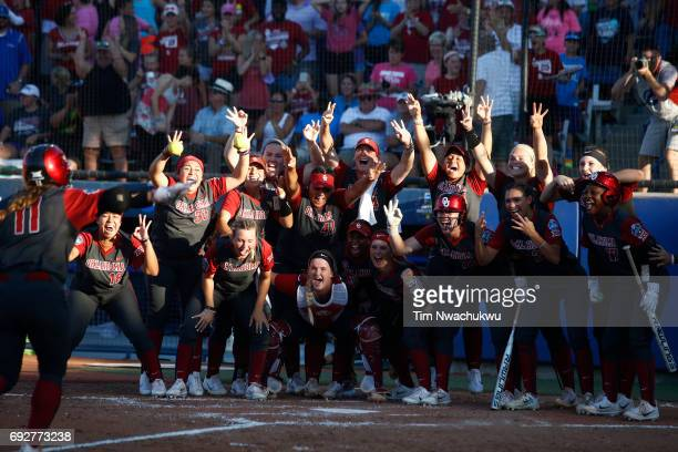 Nicole Mendes of the University of Oklahoma runs to home plate and her cheering teammates after scoring against the University of Florida during Game...