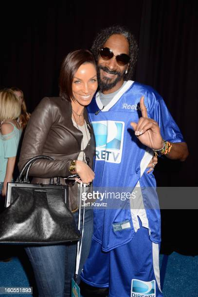 Nicole Murphy and Snoop Dogg attend DIRECTV'S 6th Annual Celebrity Beach Bowl at DTV SuperFan Stadium at Mardi Gras World on February 2 2013 in New...