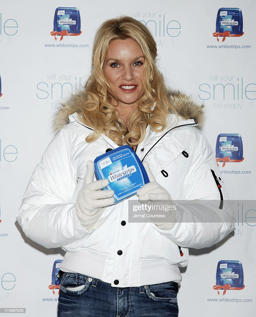 Nicollette Sheridan flashes her pearly whites for a good cause at the Crest Whitestrips Premium holiday photo booth at New York City's Wollman Rink...