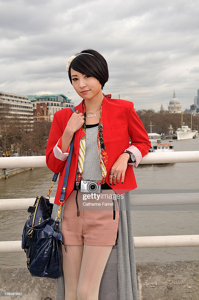 Nicosia Lok, Fashion jewellery designer, attends LWF wearing on trend Forever 21 red jacket Grey tee shirt korea, Salmon shorts with zip detail (Korea), salmon tights, Leica camera accessoried with vintage print scarf and Miu Miu bag at London Fashion Week Autumn/Winter 2012 at on February 22, 2012 in London, England.