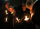 Nida Allam a senior at North Carolina State University rests her head on Asheen Allam during a candlelight vigil for murder victims Deah Barakat his...