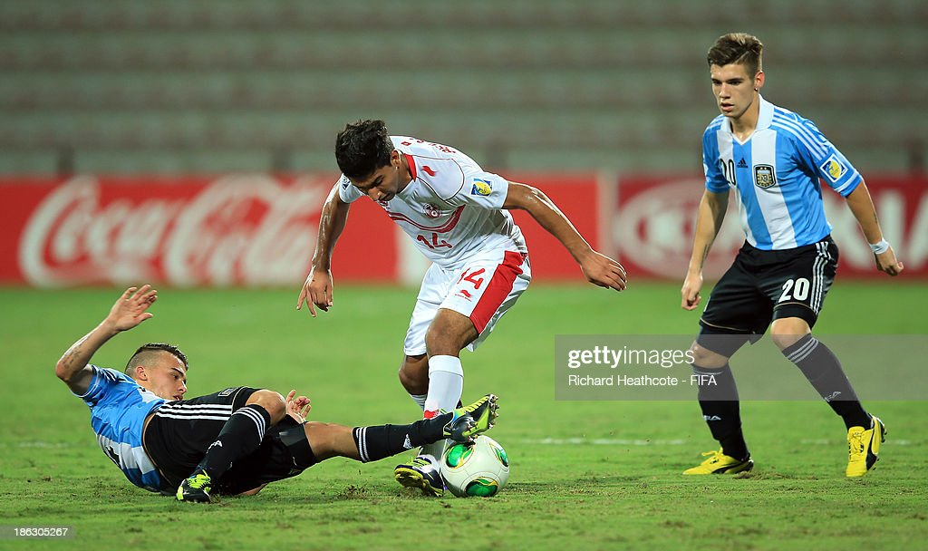 Nidhal Ben Salem of Tunisia is tackled by Lucio Compagnucci of Argentina during the FIFA U-17 World Cup UAE 2013 round of 16 match between Argentina and Tunisia at the Rashid Stadium on October 29, 2013 in Dubai, United Arab Emirates.