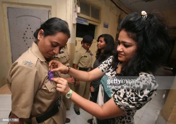 Nidhi Shah sticks a sticker saying Superhero on Woman Police Constable Shubhangi Chavan Students of Rotaract Club of Lala Lajpatrai College thanked...