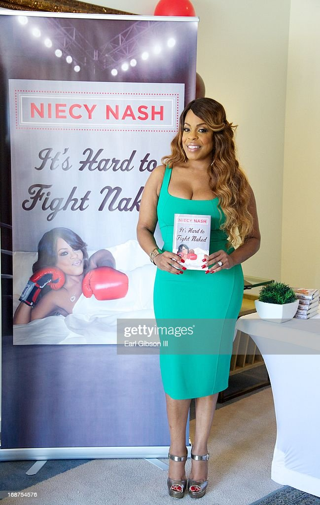 Niecy Nash holds a copy of her new book 'It's hard to Fight Naked' at Luxe Rodeo Drive Hotel on May 14, 2013 in Beverly Hills, California.