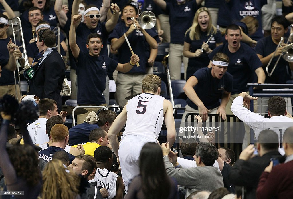 Niels Giffey #5 of the Connecticut Huskies climbs into the stands following their last second win against the Florida Gators during the game at Harry A. Gampel Pavilion on December 2, 2013 in Storrs, Connecticut.