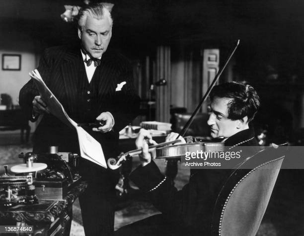 Nigel Bruce and Basil Rathbone working on sheet music together in a scene from the film 'Sherlock Holmes And The Voice Of Terror' 1942