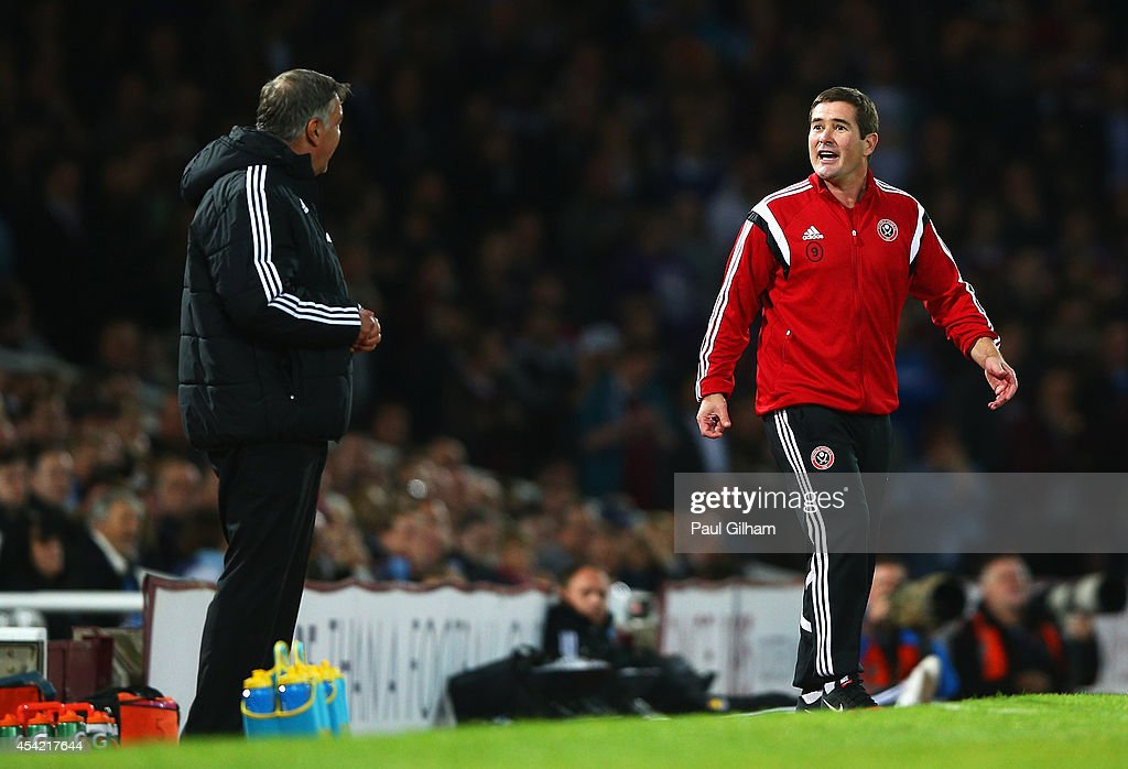 Nigel Clough, manager of Sheffield United talks to Sam Allardyce, manager of West Ham United during the Capital One Cup Second Round match between West Ham United and Sheffield United at Boleyn Ground on August 26, 2014 in London, England.