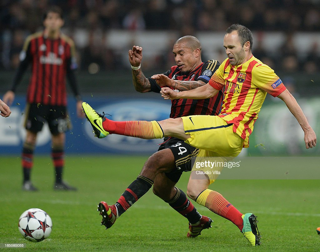 Nigel de Jong of AC Milan and <a gi-track='captionPersonalityLinkClicked' href=/galleries/search?phrase=Andres+Iniesta&family=editorial&specificpeople=465707 ng-click='$event.stopPropagation()'>Andres Iniesta</a> of FC Barcelona (R) compete for the ball during the UEFA Champions League Group H match between AC Milan and Barcelona at Stadio Giuseppe Meazza on October 22, 2013 in Milan, Italy.