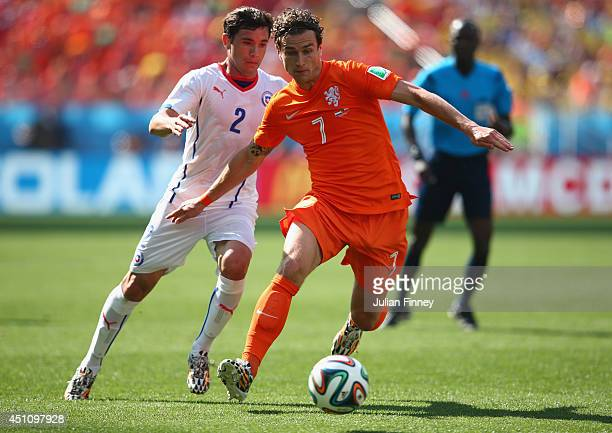 Nigel de Jong of the Netherlands controls the ball past Eugenio Mena of Chile during the 2014 FIFA World Cup Brazil Group B match between the...