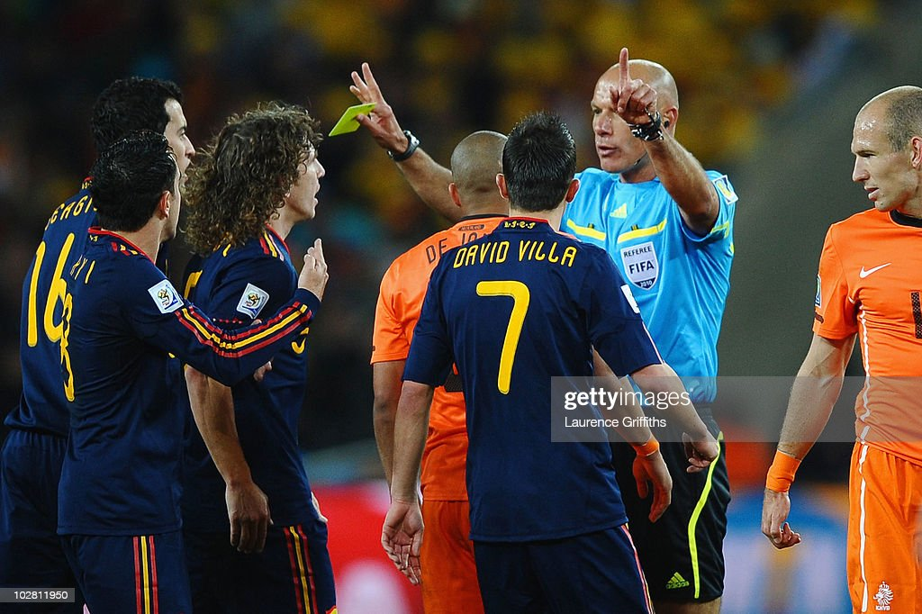 Nigel De Jong of the Netherlands receives a yellow card from Referee Howard Webb for a kick in the chest on Xabi Alonso of Spain during the 2010 FIFA...