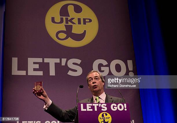 Nigel Farage holds up a British Passport which he would like to see without European Union written on during his speach at the UKIP Spring Conference...