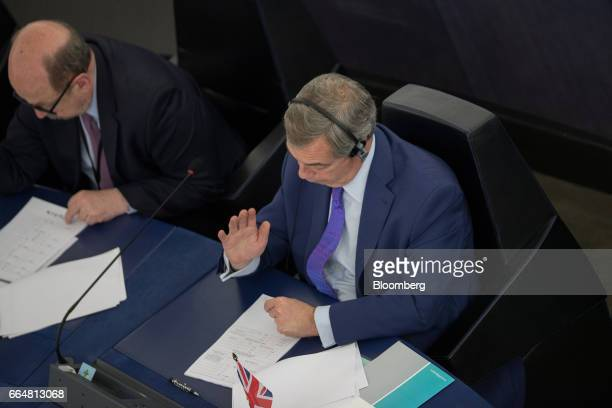 Nigel Farage member of European Parliament and former leader of the UK Independence Party raises his hand to vote for the UK's Brexit resolution...