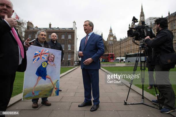 Nigel Farage speaks to the media and Satirical artist Kaya Mar outside the Houses of Parliament on March 29 2017 in London England Today British...