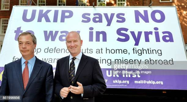 Nigel Farage the Leader of UKIP with Deputy Leader Paul Nuttall standing in front of a poster on a van that states the party's stand on any possible...