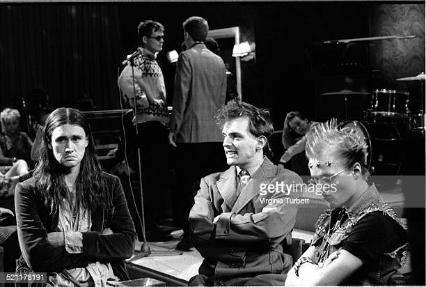 Nigel Planer as Neil Rik Mayall as Rick and Adrian Edmondson as Vyvyan with members of the band Madness behind on set during the filming of The Young...