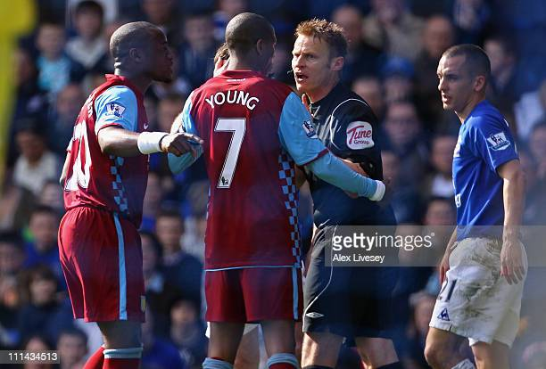 Nigel ReoCoker and Ashley Young of Aston Villa talk to referee Mike Jones during the Barclays Premier League match between Everton and Aston Villa at...
