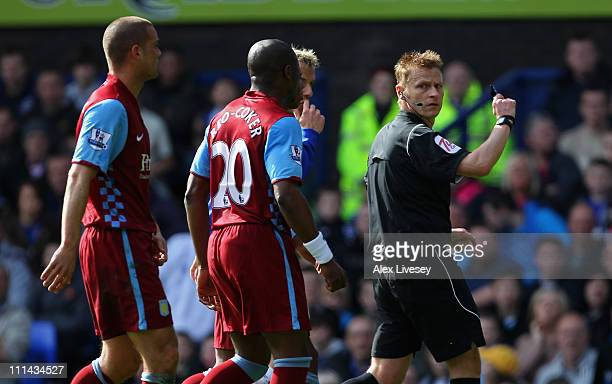 Nigel ReoCoker and Luke Young of Aston Villa question a decision from referee Mike Jones during the Barclays Premier League match between Everton and...