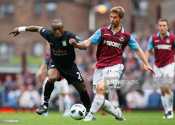 Nigel ReoCoker of Aston Villa is tackled by Thomas Hitzlsperger of West Ham United during the Barclays Premier League match between West Ham United...