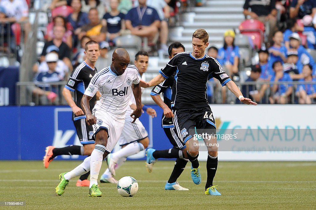 Nigel ReoCoker of the Vancouver Whitecaps carries the ball against Clarence Goodson of the San Jose Earthquakes during an MLS match at BC Place on...