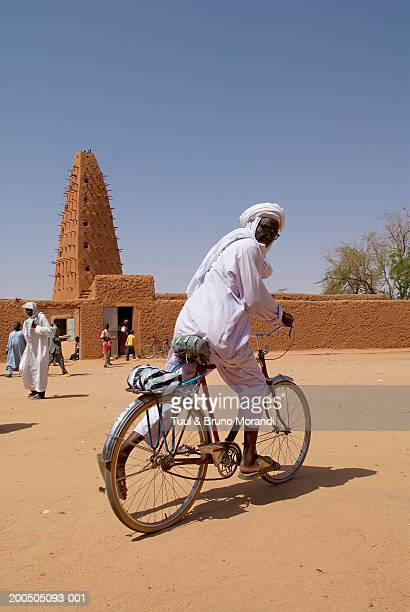 Niger, Agadez, man on bicycle outside The Great Mosque