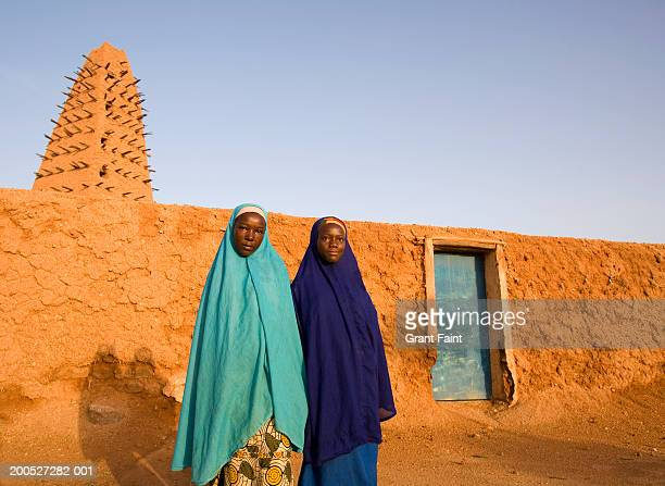 Niger, Agadez, Two muslim women standing in front of mosque
