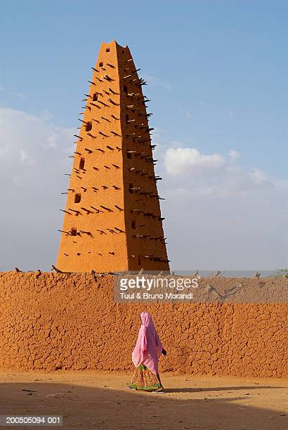 Niger, Agadez, woman walking outside The Great Mosque
