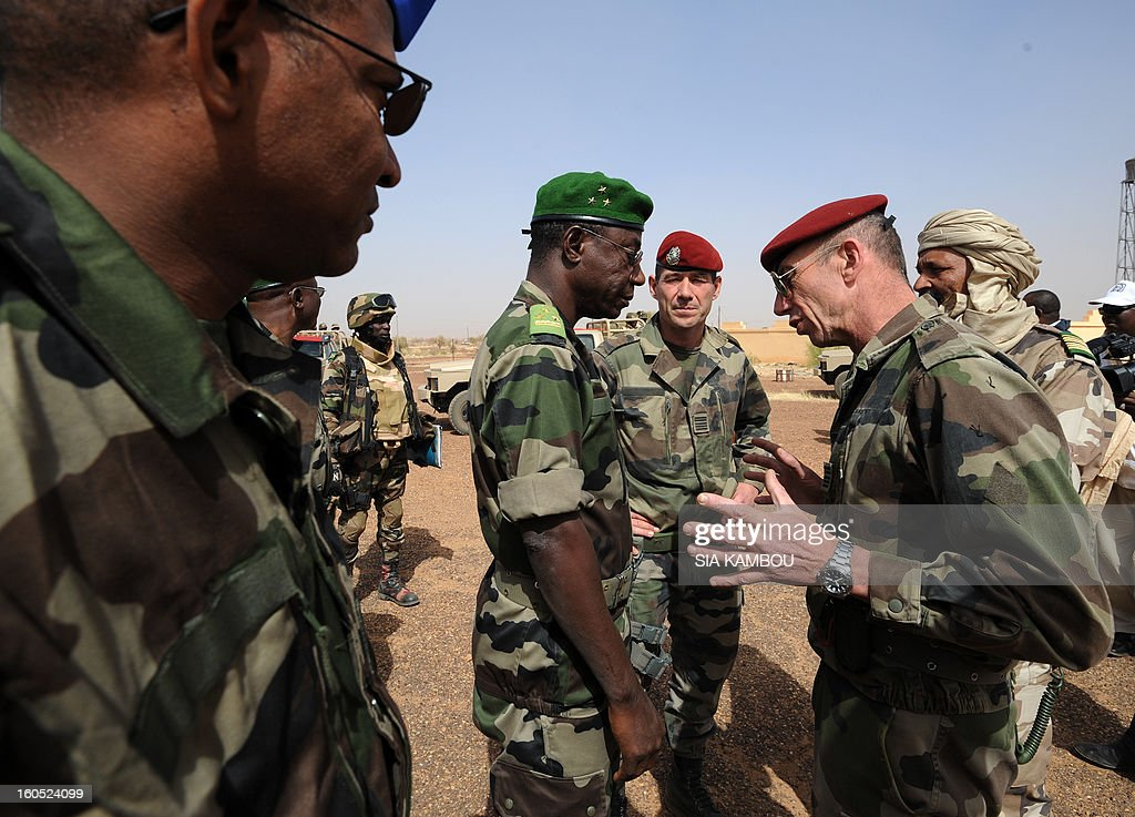 Niger army chief of staff Seini Garba (2ndL) listens to French Colonel Zavier (R) on February 2, 2013 in Gao. French President Francois Hollande received a rapturous welcome as he visited Mali to push for African troops to take over a French-led offensive that drove back Islamist rebels from the country's desert north. AFP PHOTO / SIA KAMBOU