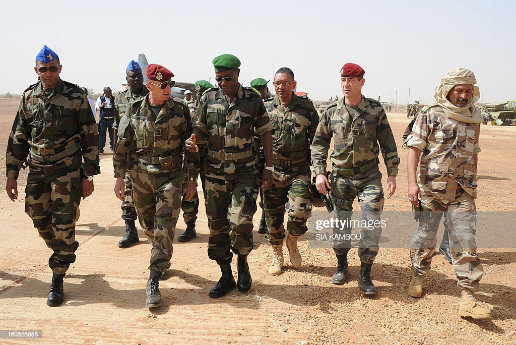 Niger army chief of staff Seini Garba (3rdL) speaks with French Colonel Zavier (2ndL), flanked by Mali's army colonel El Hadj Ag Gamou (R), on February 2, 2013 in Gao. French President Francois Hollande received a rapturous welcome as he visited Mali to push for African troops to take over a French-led offensive that drove back Islamist rebels from the country's desert north.