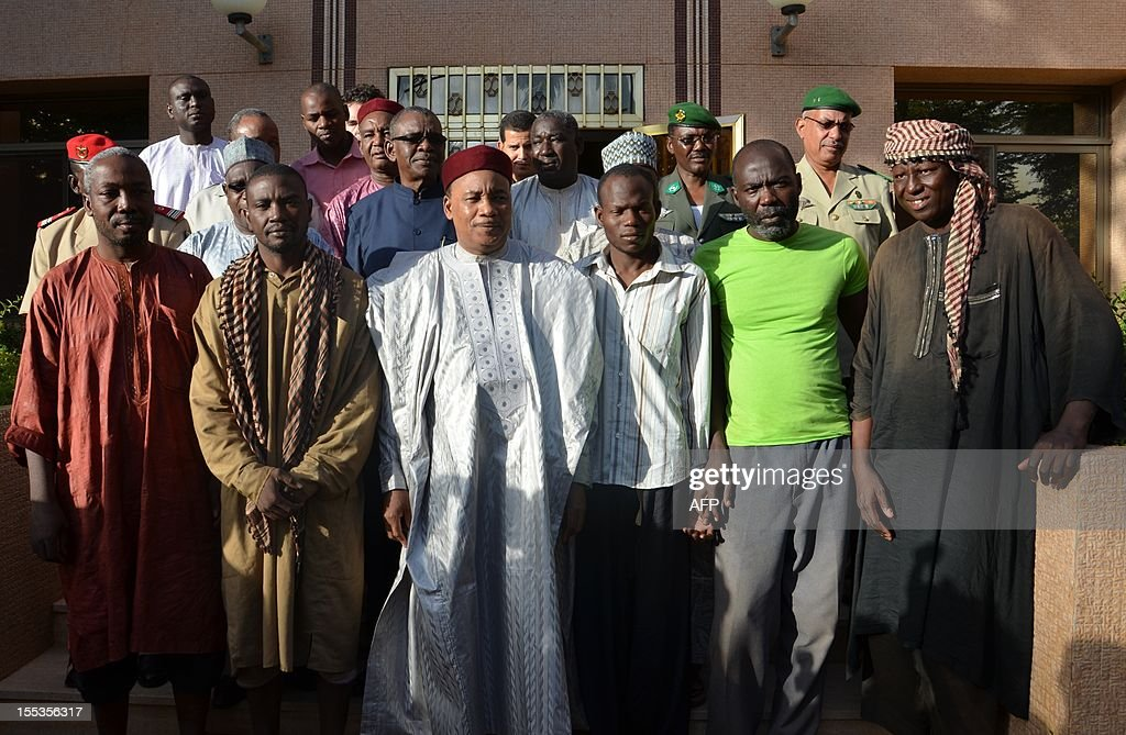 Niger President Mahamadou Issoufou (C) poses on November 3, 2012 with four of five African aid workers who were abducted in Niger in mid-October and were recently freed at the presidential palace in Niamey. The five African aid workers were freed alive, while a sixth died after being shot by the Al-Qaeda-linked kidnappers, officials said the workers and their employers said on November 3. One of the hostages said the kidnapping was carried out by the armed Islamist group Movement for Oneness and Jihad in West Africa (MUJAO), one of the Al-Qaeda-backed groups that have seized control of the north in neighbouring Mali.