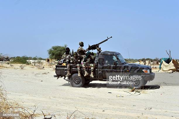 Niger soldiers ride in a military vehicle on May 25 2015 in Malam Fatori in northern Nigeria near the border with Niger where the Niger and Chadian...