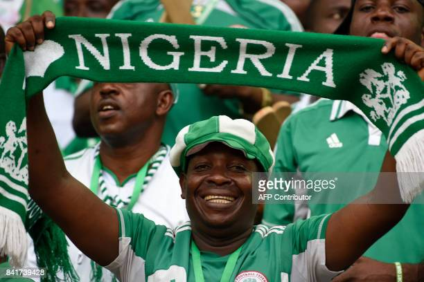 Nigeria fans cheer during the 2018 FIFA World Cup qualifying football match between Nigeria and Cameroon at Godswill Akpabio International Stadium in...
