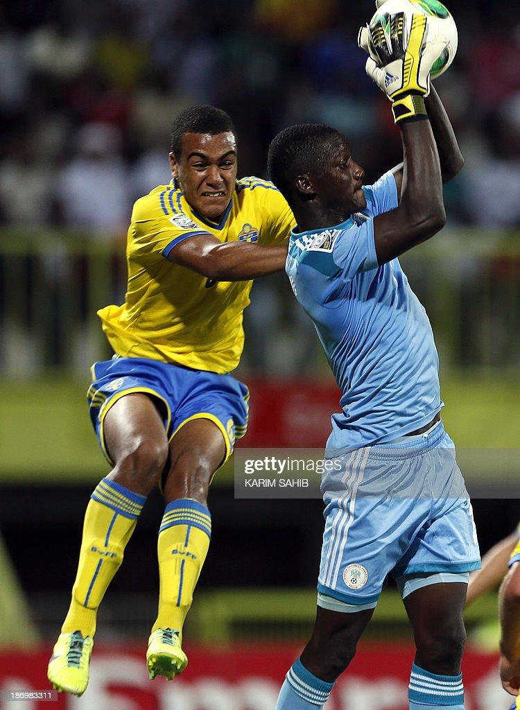 Nigeria goal keeper Dele Alampasu (R) defends as Noah Sonko of Sweden jumps to the ball during the two teams' semi-final in the FIFA U-17 World Cup in Dubai's Rashid Stadium, on November 5, 2013.