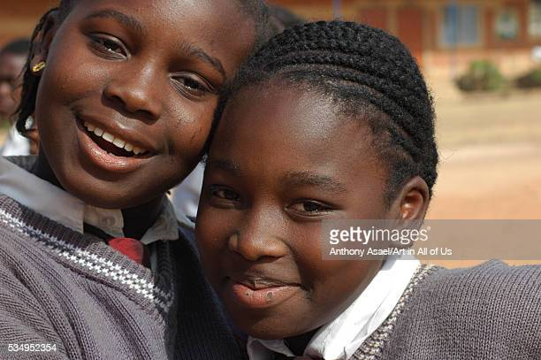 Nigeria Jos Portrait of schoolgirls in their purple uniform smiling and laughing embracing each other