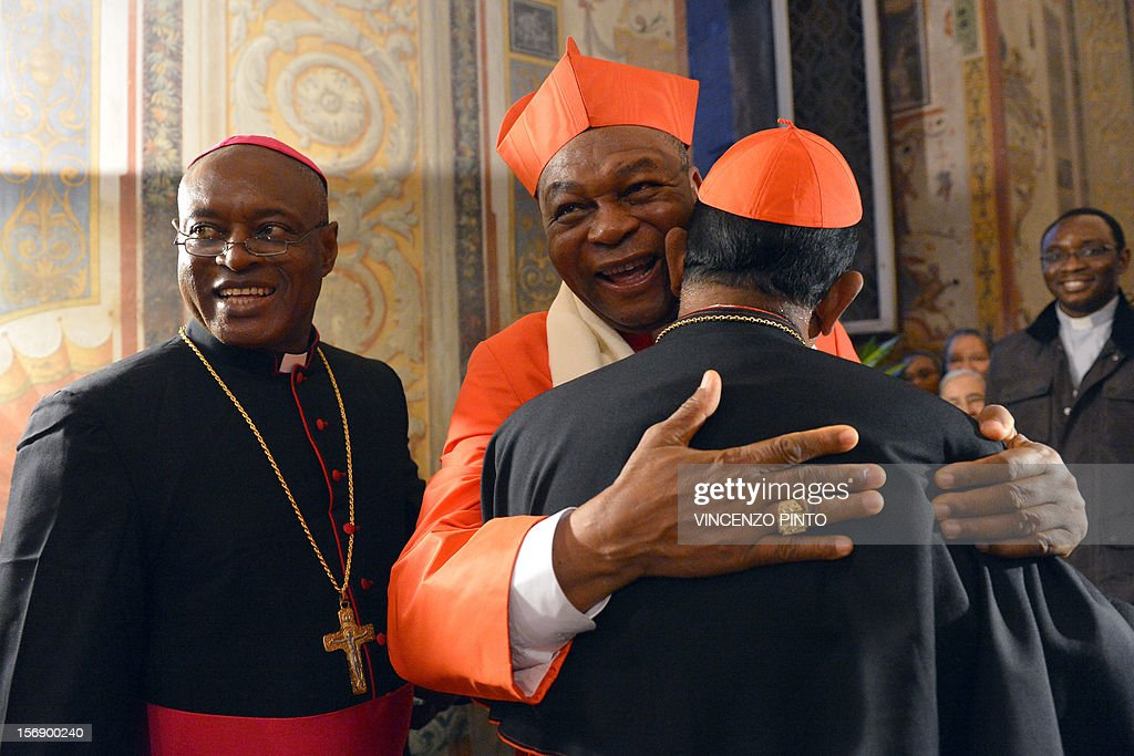 Nigerian cardinal John Onaiyekan (C) greets visitors druing the courtesy visit after being appointed by the pontif on November 24, 2012 at the Apostolico palace at the Vatican. Six non-European prelates are set to join the Catholic Church's College of Cardinals, a move welcomed by critics concerned that the body which will elect the future pope is too Eurocentric.