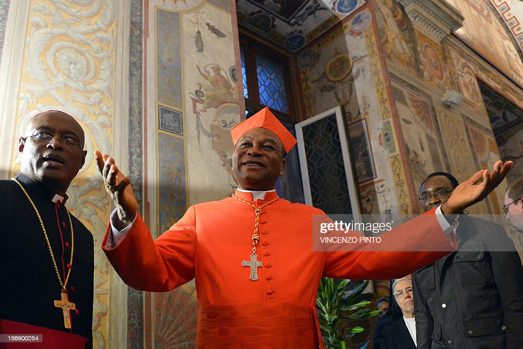 Nigerian cardinal John Onaiyekan (C) greets visitors during the courtesy visit after being appointed by the pontif on November 24, 2012 at the Apostolico palace at the Vatican. Six non-European prelates are set to join the Catholic Church's College of Cardinals, a move welcomed by critics concerned that the body which will elect the future pope is too Eurocentric.