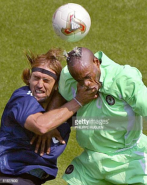 Nigerian defender Taribo West and Argentinian forward Gabriel Batistuta collide as they head the ball during the Argentina/Nigeria Group F match of...