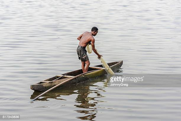Nigerian fisherman pulling his fishing net from the water, Lagos