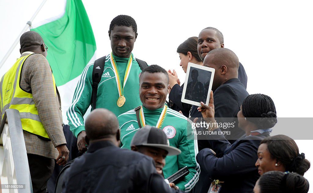 Nigerian football team joint highest goal scorer Emmanuel Emenike (C) alights from the plane in Abuja February 12, 2013. The newly crowned African champions Nigerian Super Eagles arrives in Abuja to a warm reception by fans and government officials after defeating Burkina Faso to win the 2013 African Cup of Nations in South Africa.