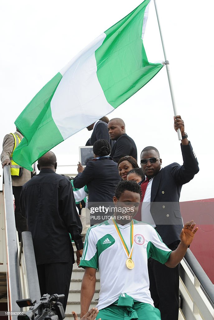 Nigerian football team midfielder Mikel Obi (C-bottom) alights from the plane in Abuja, on February 12, 2013. The newly crowned African champions Nigerian Super Eagles arrives in Abuja to a warm reception by fans and government officials after defeating Burkina Faso to win the 2013 African Cup of Nations in South Africa.