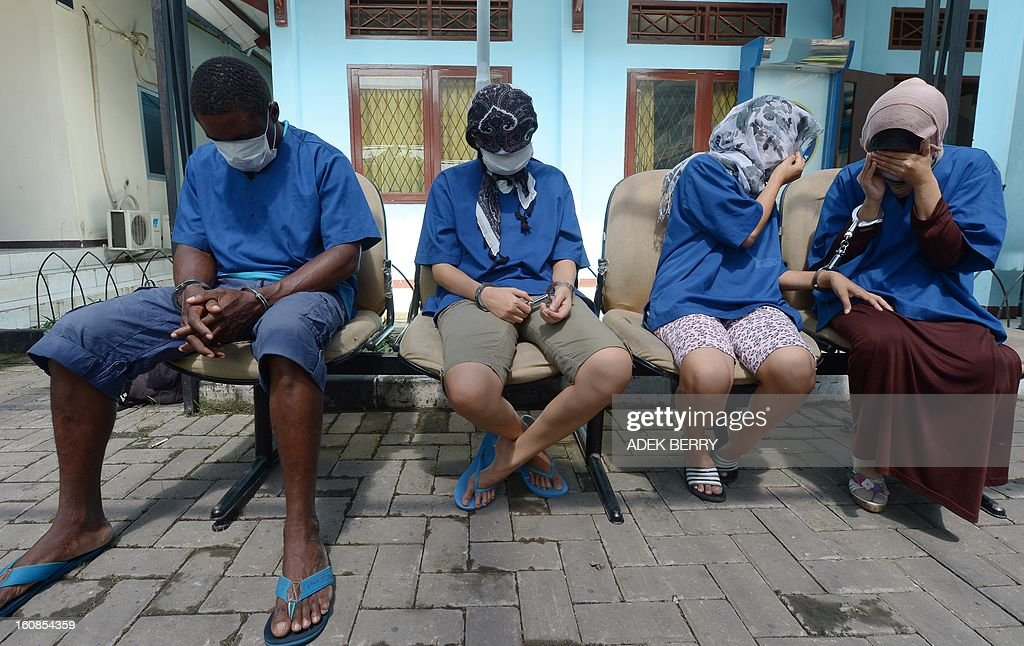 A Nigerian man (L) and Indonesian women (R) suspects for drug couriers cover their faces during a press conference in Jakarta on February 7, 2013. Indonesian authorities destroyed about 3 kilograms shabu confiscated during recents anti-drugs operation where syndicates are using women as drugs couriers.