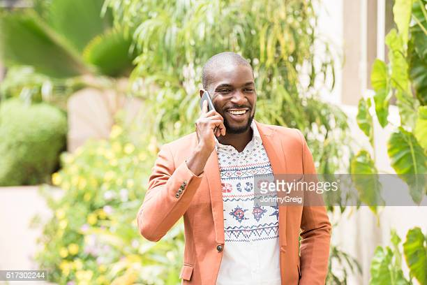 Nigerian man in orange jacket on cell phone, smiling