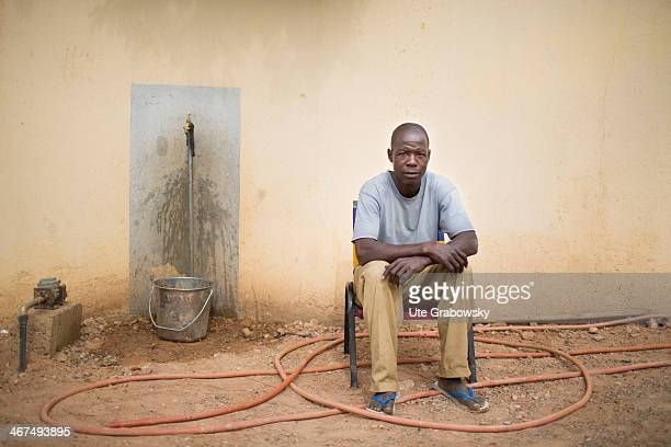 Nigerian man selling drinking water he is sitting in front of a water tap and bucket on December 04 in Niamey Niger Photo by Ute Grabowsky/Photothek...