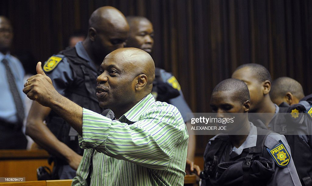 Nigerian militant leader Henry Okah (L) gives a thumbs up in the courtroom after his case was posted because he changed his legal team at Johannesburg High Court on February 28, 2013. Okah is convicted of 13 terrorism charges, including the 2010 independence day bombings in Abuja. Okah was found guilty of masterminding attacks including twin car bombings in Abuja on October 1, 2010, and two explosions in March 2010 in the southern Nigerian city of Warri, a major hub of the oil-rich Delta region. He faces a minimum term of life in prison.